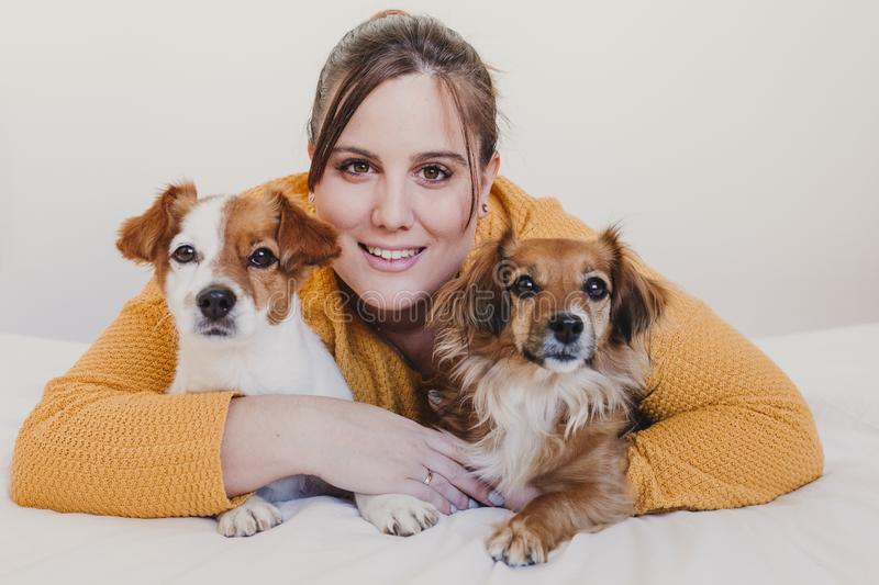 Young woman and her cute dog sitting on bed. love for animals concept. top view. Portrait of a young woman and her cute two dogs sitting on bed. love for animals royalty free stock photos