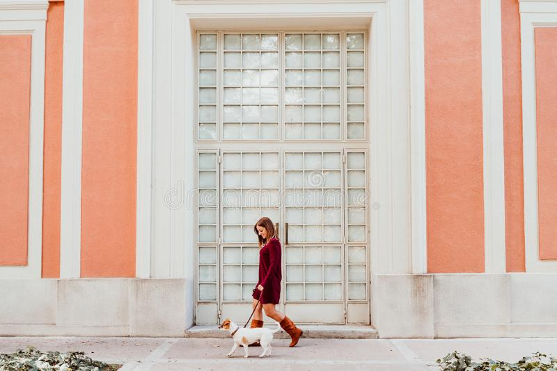young woman and her cute jack russell dog walking by the city. Love for animals concept royalty free stock photography
