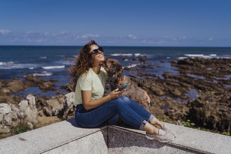 Young woman and her cute spanish water dog outdoors enjoying together on a sunny and windy day. Summertime, love for animals and royalty free stock photos
