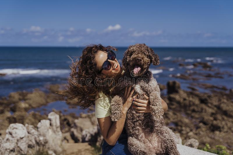 Young woman and her cute spanish water dog outdoors enjoying together on a sunny and windy day. Summertime, love for animals and stock photo