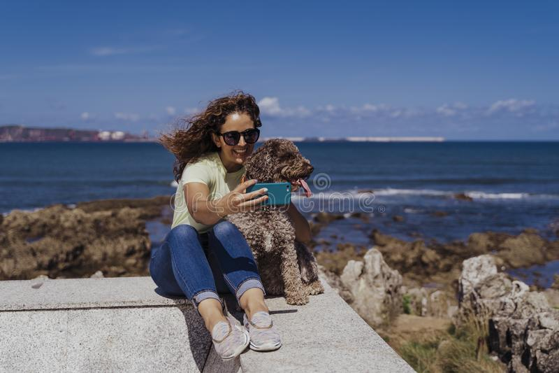 Young woman and her cute spanish water dog outdoors enjoying together on a sunny and windy day. Woman taking selfie with mobile royalty free stock image