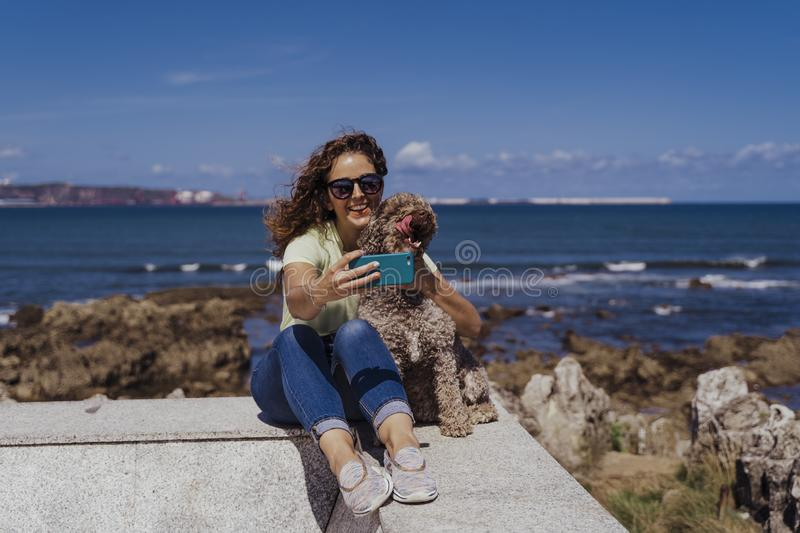 Young woman and her cute spanish water dog outdoors enjoying together on a sunny and windy day. Woman taking selfie with mobile royalty free stock images