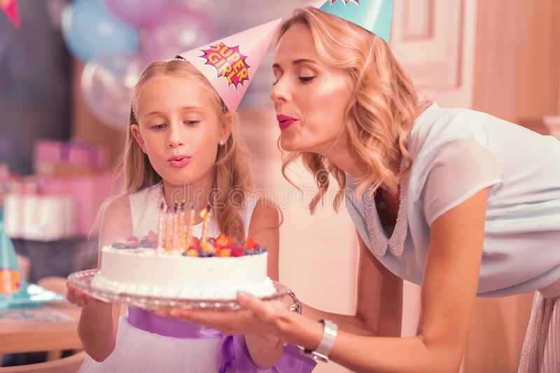 Young woman and her daughter blowing candles on the birthday cake. Candles on cake. Calm young women holding birthday cake and blowing candles on it together stock image