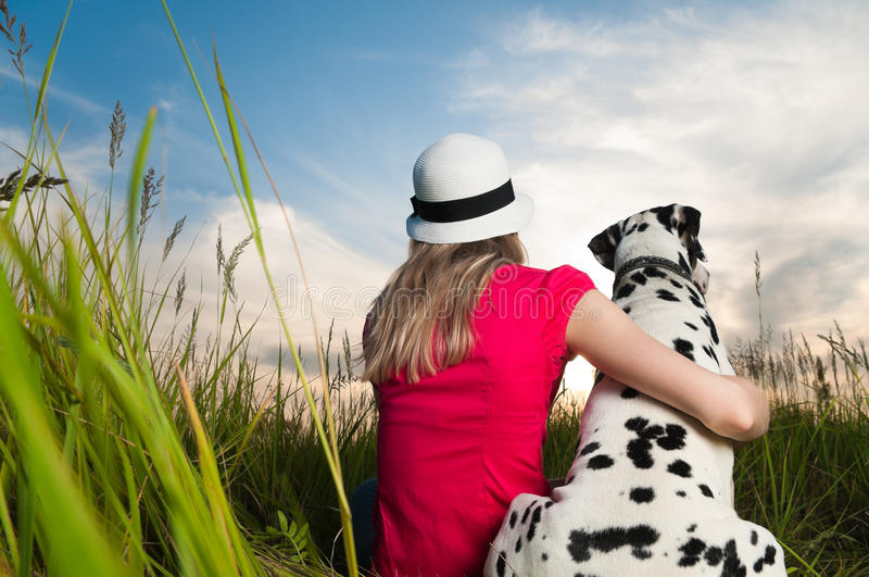 Young woman with her dog pet. Beautiful young woman in hat sitting in grass with her dalmatian dog pet with their backs to camera. Sunset cloudy sky in royalty free stock photo