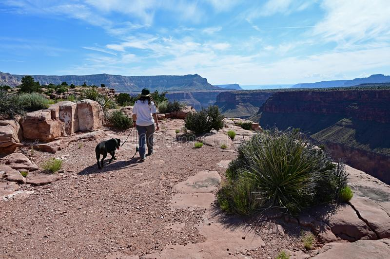 Young woman with her dog at Toroweap in the Grand Canyon. Young woman walks her dog on the rugged roads and trails at Toroweap in Grand Canyon National Park royalty free stock image
