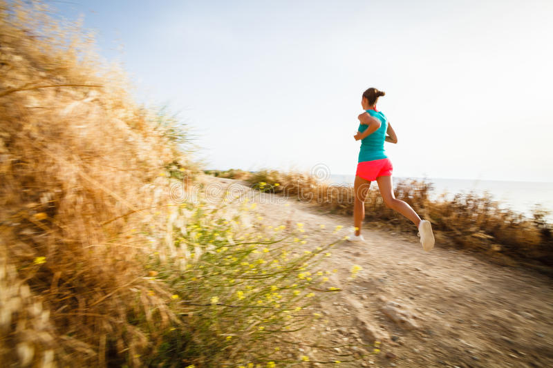 Young woman on her evening jog along the seacoast. (motion blurred image royalty free stock photo