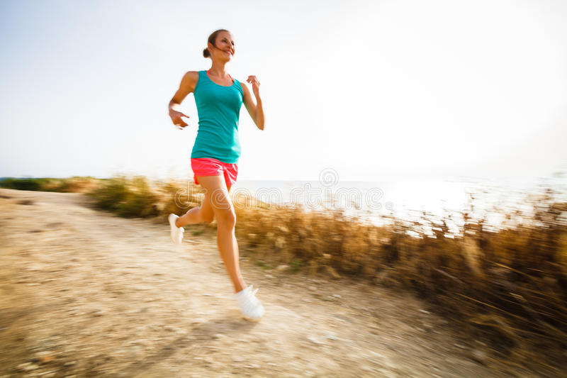 Young woman on her evening jog along the seacoast. (motion blurred image royalty free stock photography