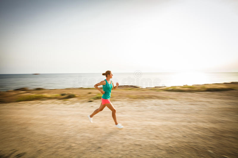 Young woman on her evening jog along the seacoast. (motion blurred image royalty free stock images