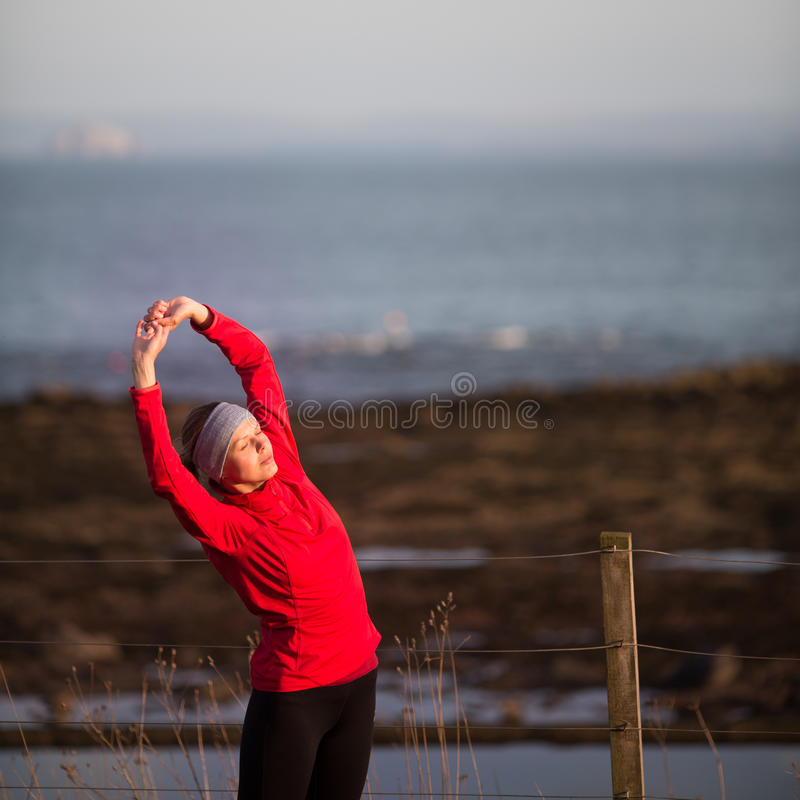 Young woman on her evening jog. Along the seacoast royalty free stock image