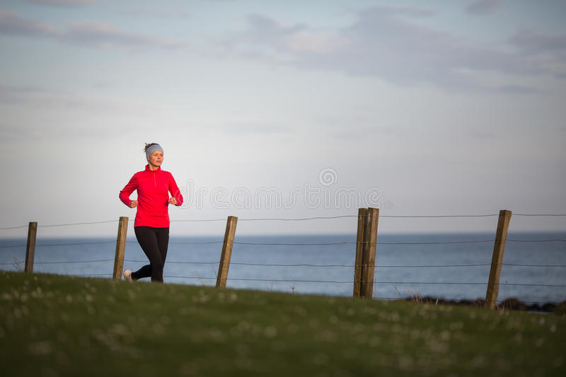 Young woman on her evening jog. Along the seacoast stock photography