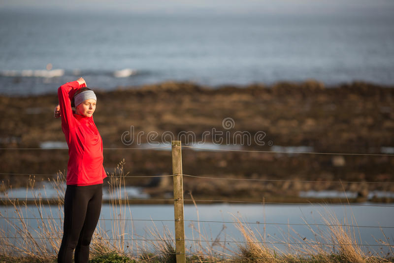 Young woman on her evening jog. Along the seacoast royalty free stock photos