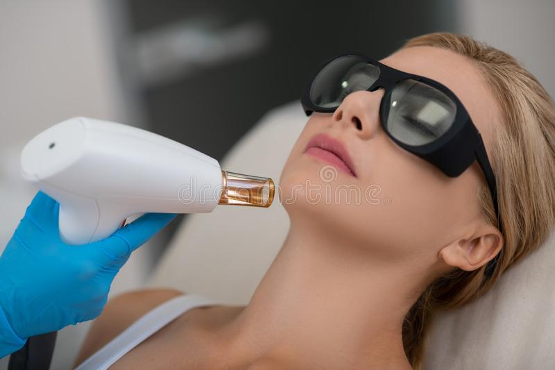 Young woman during her facial procedures at beauty salon. stock photography