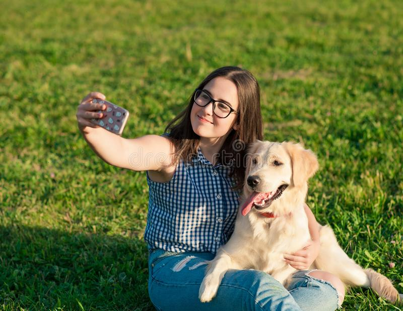Young woman and her friendly dog taking a selfie at a park stock photography