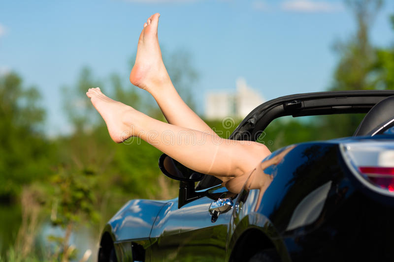 Young woman or her legs in a cabriolet stock photography