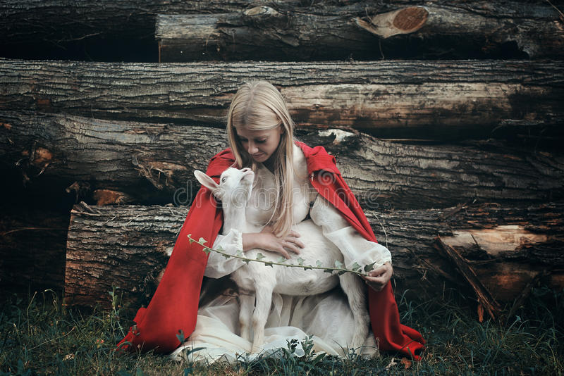 Young woman and her little goat royalty free stock image