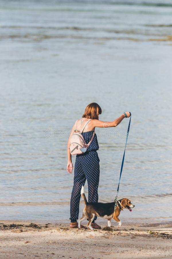 Young woman with her lovely beagle dog on the beach of Bali island, Indonesia. royalty free stock photography