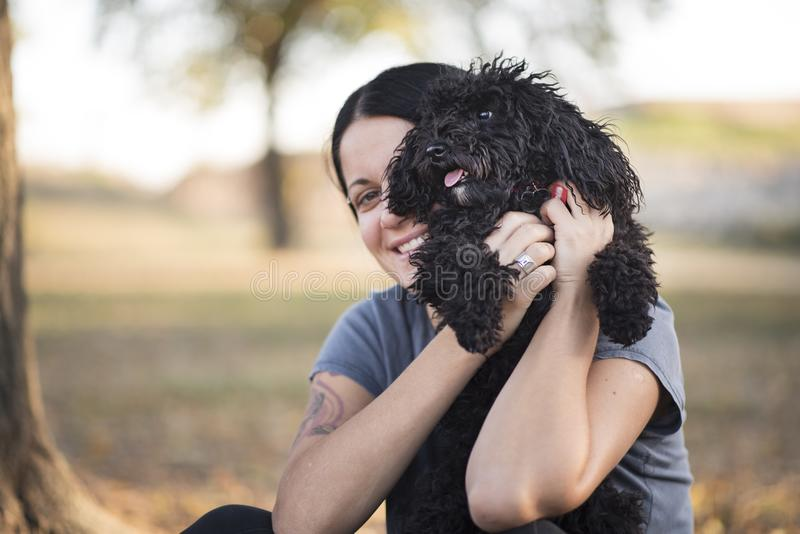 Young woman and her poodle puppy stock image