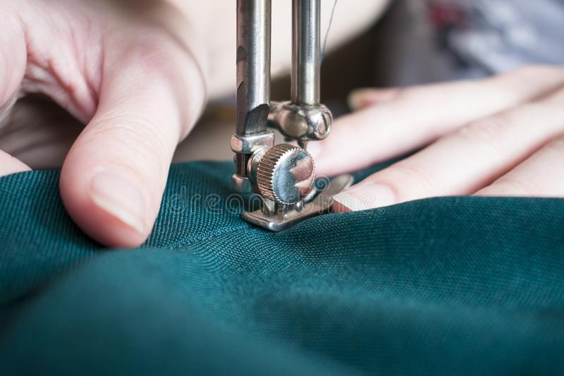 Young woman on her sewing process, women`s hands behind her working on sewing machine. Closeup side royalty free stock photos