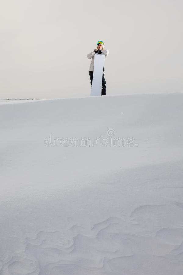 Young woman and her snowboard on snow-covered mountainside royalty free stock image