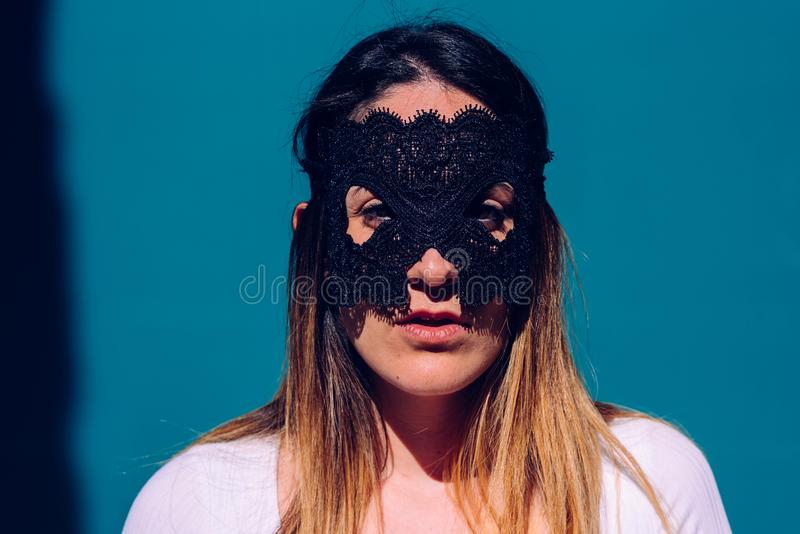 Young woman hides her face behind a mask to escape from stalkers, seeking anonymity and privacy stock photo