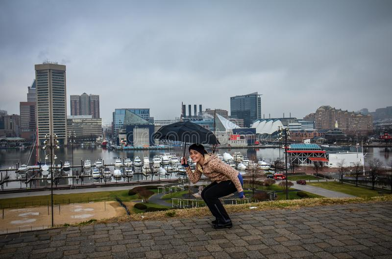 Young woman hides under an umbrella on a gloomy, rainy day in Inner Harbor Baltimore. Concept for inclement weather royalty free stock photography