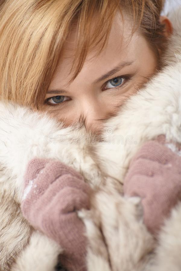 Young woman hiding her face in fur coat
