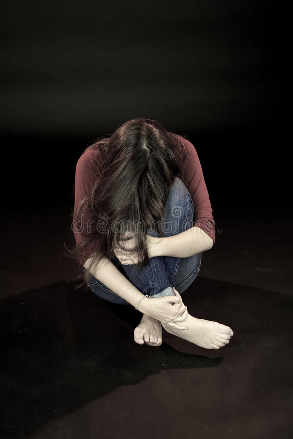 Young woman hiding scared about domestic violence stock photography