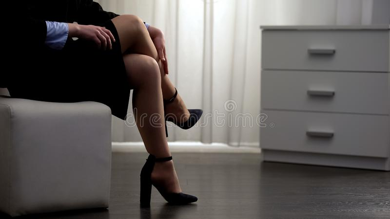 Young woman in high heeled shoes sexually stroking leg, art of seduction. Stock photo royalty free stock photography