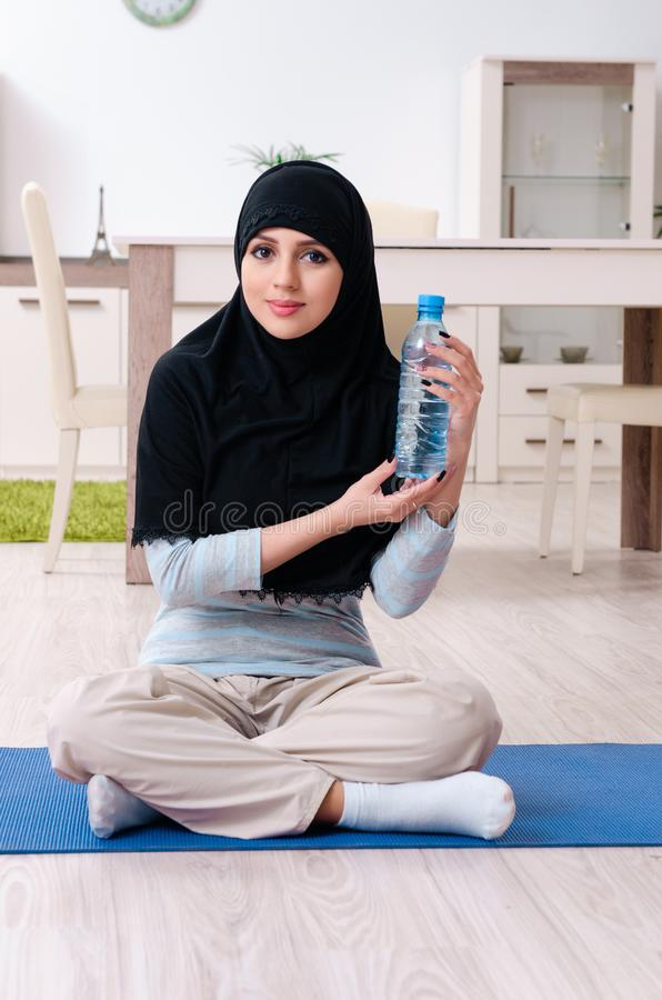 Young woman in hijab doing exercises at home stock images