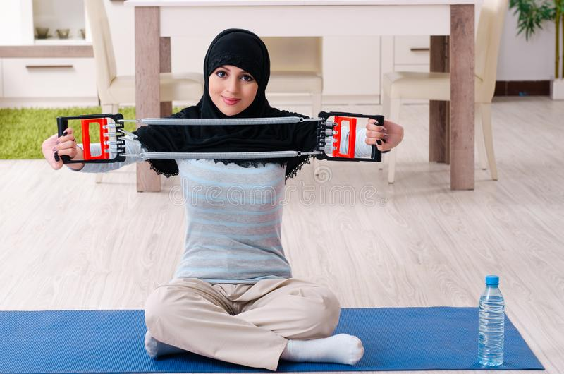 Young woman in hijab doing exercises at home royalty free stock images