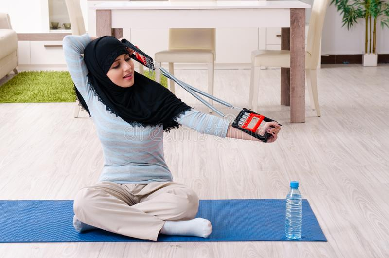 Young woman in hijab doing exercises at home royalty free stock photo