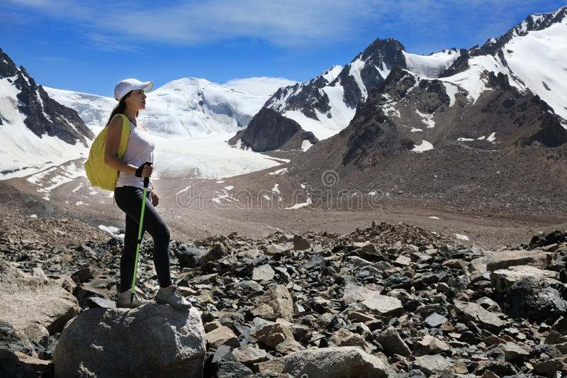 Young woman hiker with backpack in the mountains with glaciers royalty free stock image