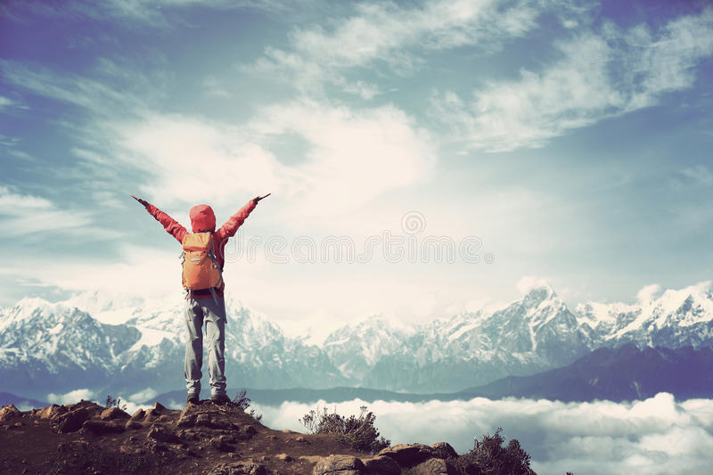 Young woman hiker open arms to beautiful snow mountain summits royalty free stock images
