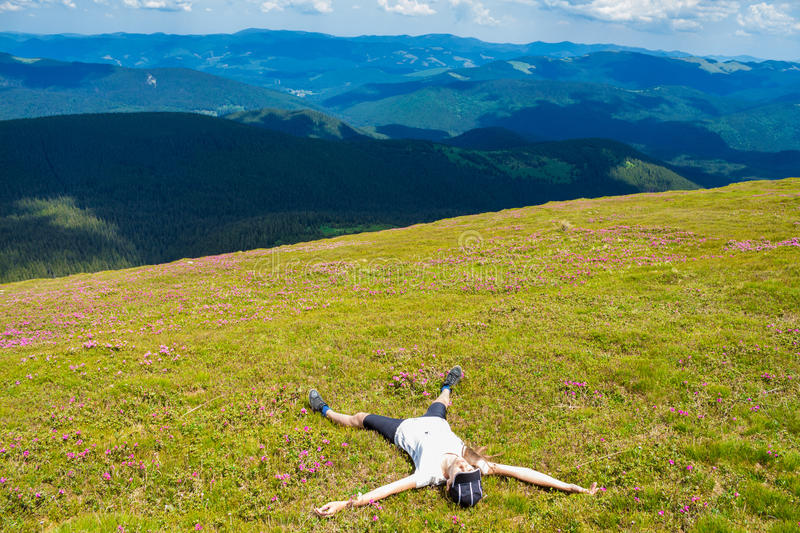 Young woman hiker relaxing on the top of hill and admiring beautiful mountain valley view royalty free stock image