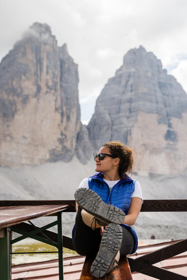 Young woman hiker resting near famous rock formation Tre Cime royalty free stock image