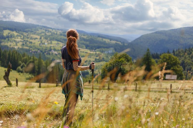 Young woman hiker standing admiring a mountain view looking out over distant ranges of mountains and valleys. Healthy lifestyle concept royalty free stock images