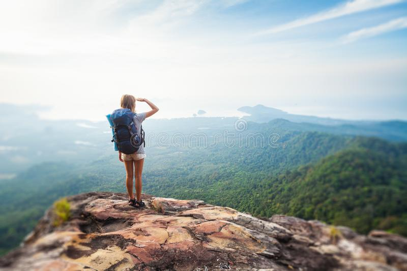 Young woman hiker. Stands with backpack on the cliff and looks into valley and sea coastline. Tilt shift effect applied royalty free stock photo