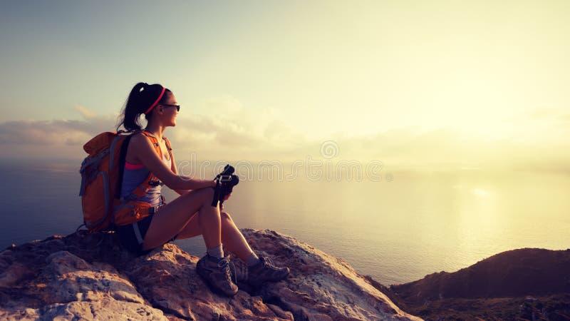 Woman hiker at sunrise seaside mountain peak royalty free stock images