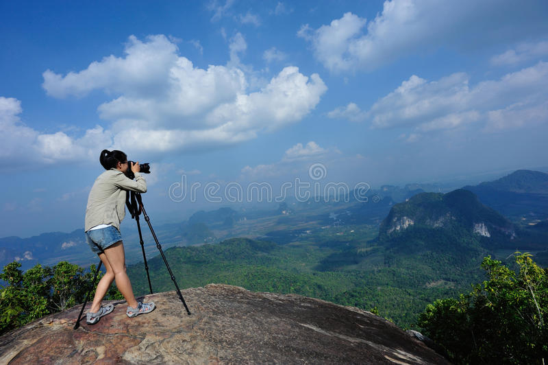 Young woman hiker taking photo with dslr camera. At mountain peak royalty free stock images