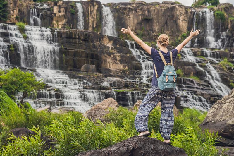 Young woman hiker, tourist on the background of Amazing Pongour Waterfall is famous and most beautiful of fall in. Vietnam. Not far from Dalat city estimate 45 stock photo