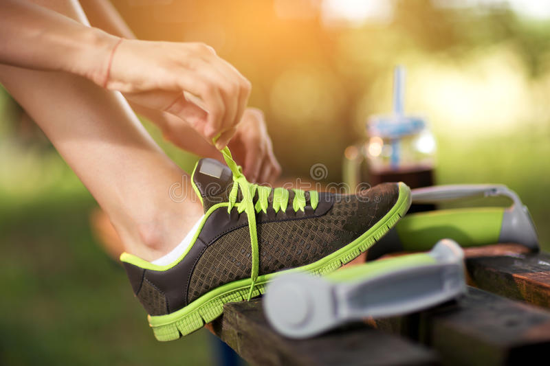 Young woman hiker tying shoelaces stock photos