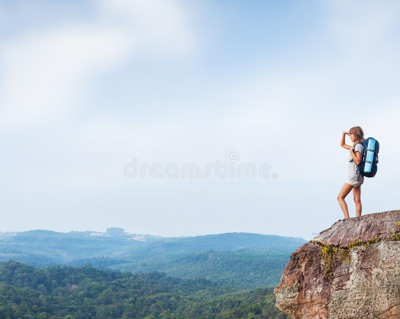 Young woman hiker. Stands with backpack on the cliff and looks into valley royalty free stock photos