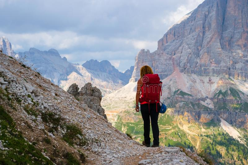 Young woman hiking in the Dolomites mountains, Italy, on Giro delle Cinque Torri, with storm clouds approaching. Guiding, touring stock images