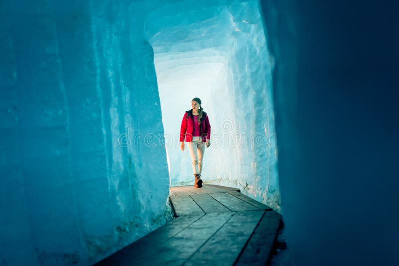 Young woman hiking through glacier cave royalty free stock photography