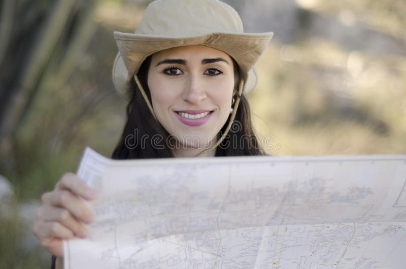 Young woman on hiking trip. Young beautiful woman looking at a map on a hiking trip stock photo