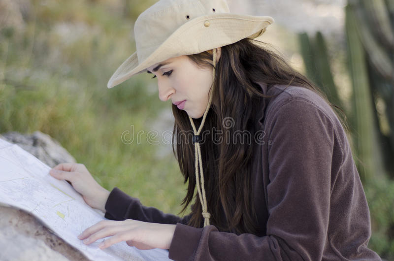 Young woman on hiking trip. Young beautiful woman looking at a map on a hiking trip royalty free stock image