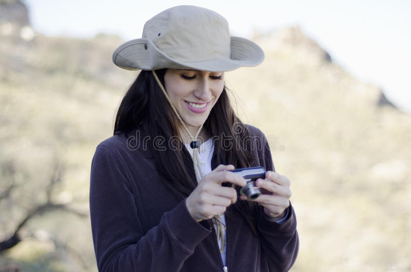 Young woman on hiking trip. Young beautiful woman taking pictures on a hiking trip royalty free stock image