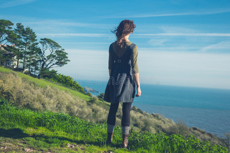 Young woman on hilltop by the sea stock photos