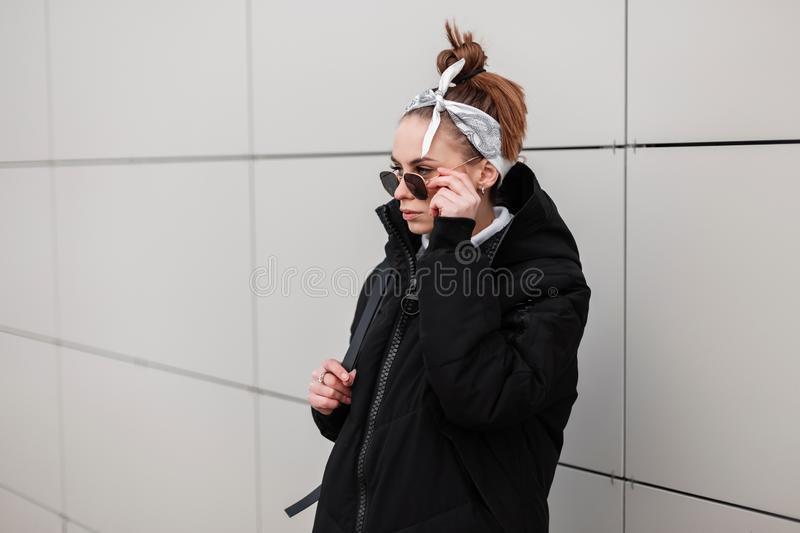 Young woman hipster in a stylish long jacket with a leather backpack with a stylish hairstyle in a trendy bandana. In black sunglasses near a white wall in the royalty free stock photos