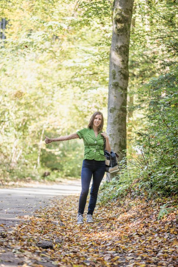 Young woman hitchhiker standing in autumn forest royalty free stock photography